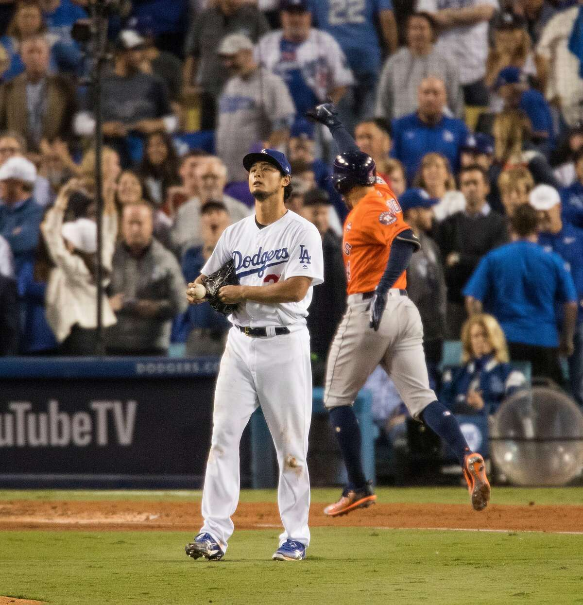 Los Angeles Dodgers starting pitcher Yu Darvish stares into the outfield as the Houston Astros' George Springer reaches home plate after hitting a two-run home run in the second inning during Game 7 of the World Series at Dodger Stadium in Los Angeles on Wednesday, Nov. 1, 2017. (Gina Ferazzi/Los Angeles Times/TNS)