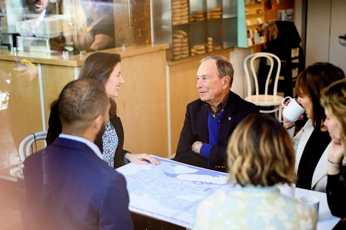 Democratic presidential candidate Michael Bloomberg speaks with Oakland Mayor Libby Schaaf, left, at Beauty's Bagel Shop in Oakland, Calif., on Friday, Jan. 17, 2020.