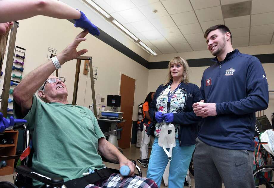 John Acerbi (left) of Litchfield meets with 2019 Walter Camp Football Foundation All-American Keith Duncan (right) of Iowa while doing exercises with occupational therapist Katie Zimmerli (far left) at the Gaylord Hospital inpatient therapy room in Wallingford on January 17, 2020. In the background is rehabilitation aid Dawn Peck. Photo: Arnold Gold / Hearst Connecticut Media / New Haven Register