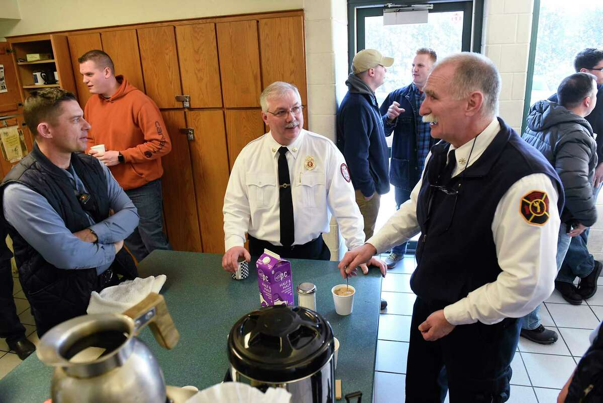 Deputy Fire Chief Tom Scorsone, center, is surrounded by co-workers and friends who came to wish him well in his retirement at the Troy Central Fire House on Friday, Jan. 17, 2020 in Troy, N.Y. (Lori Van Buren/Times Union)