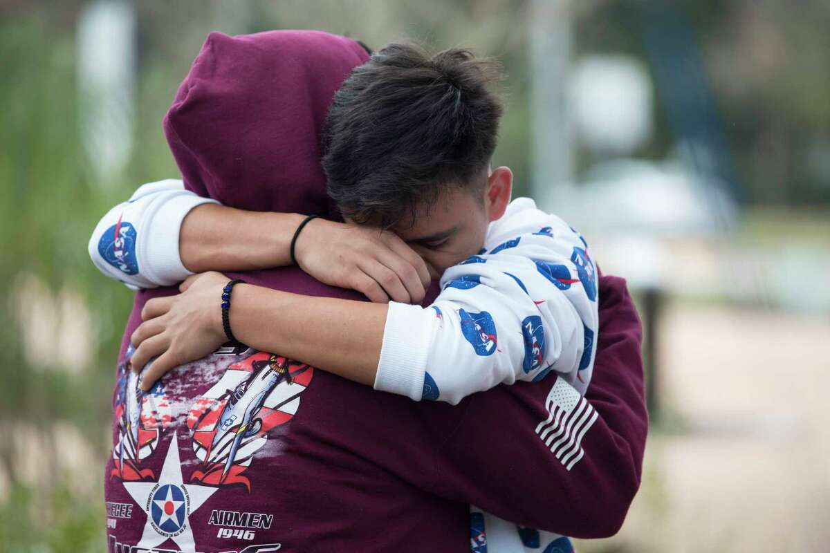Bellaire High School students Viviana De La Torre, 17, and Adrian Interiano, 16, hug and console each other while gathering to remember the student who was shot and killed yesterday on campus at Evelyn Park on Wednesday, Jan. 15, 2020, in Bellaire. The victim was in the JROTC, and was shot by another student in the corps.