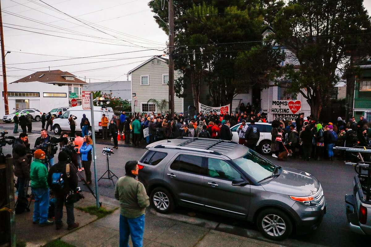 Demonstrators gather outside a home in West Oakland to show support for two homeless women have been illegally occupying a home and may soon face eviction on Monday, Jan. 13, 2020 in Oakland, California.
