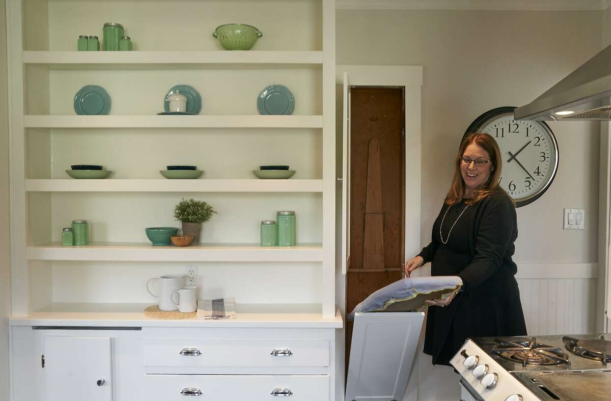 Real estate agent Shannon Prokup lowers an original ironing board at a 2 bedroom, 1 bath house she has listed on Friday, Jan. 17, 2020, in Berkeley, Calif.