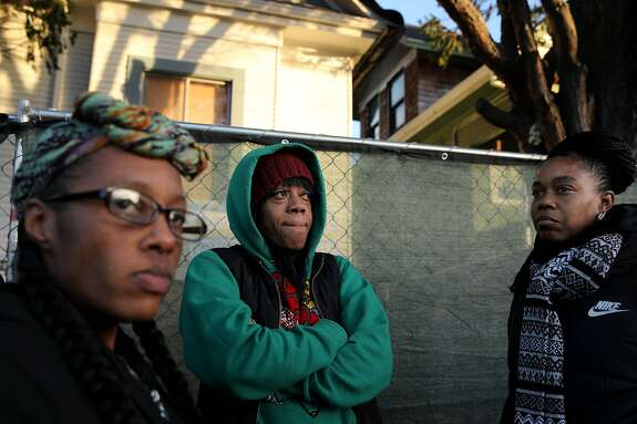 Moms 4 Housing members Dominique Walker, Misty Cross, and Tolani King stand outside the house the homeless mothers occupied in Oakland, Calif., on Tuesday, January 14, 2020. Cross and King were arrested during their eviction early on Tuesday morning.