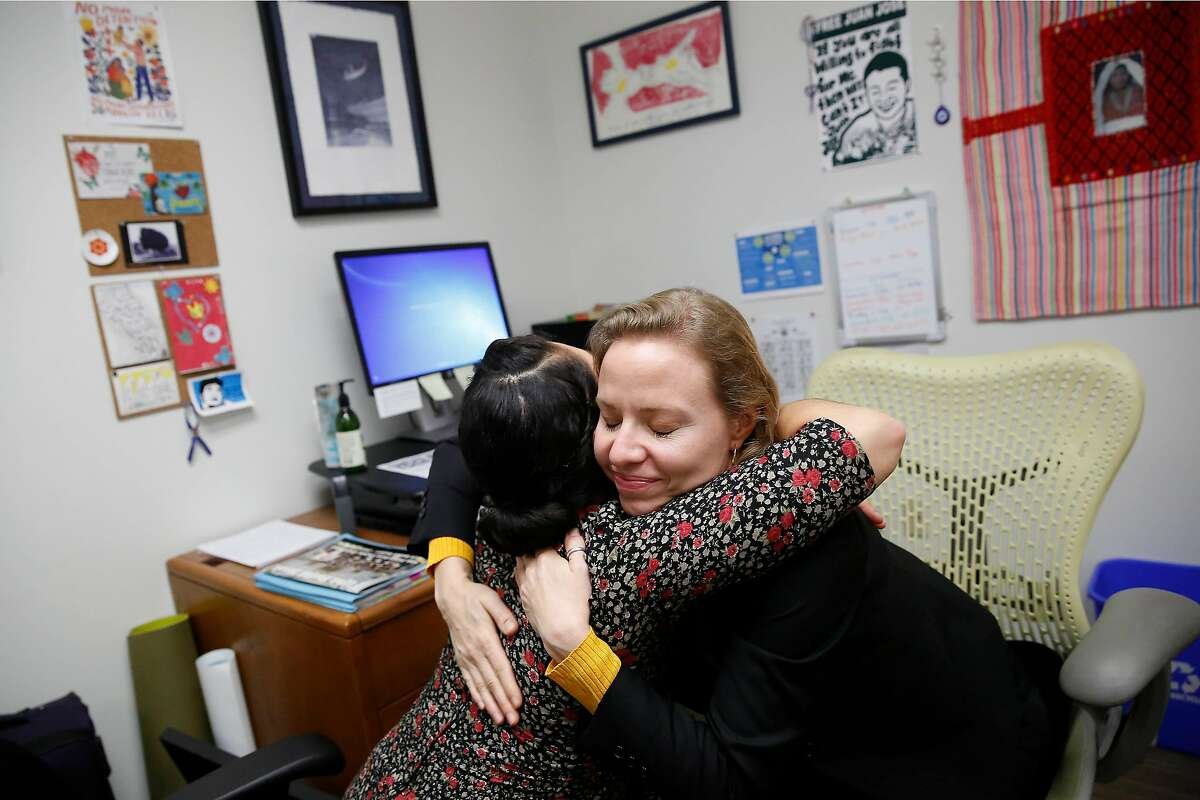 Kelly Engel Wells (right), deputy public defender, and Edie Castellon (left), immigration social worker Office of the Public Defender, hug during an emotional moment while discussing clients' cases in Wells' office at the Office of the Public Defender on Friday, January 17, 2020 in San Francisco, Calif.