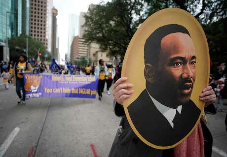 A person marches with a portrait of Martin Luther King, Jr. during the Black Heritage Society's 41st Annual Original MLK, Jr. Day Parade Monday, January 21, 2019 in Houston.