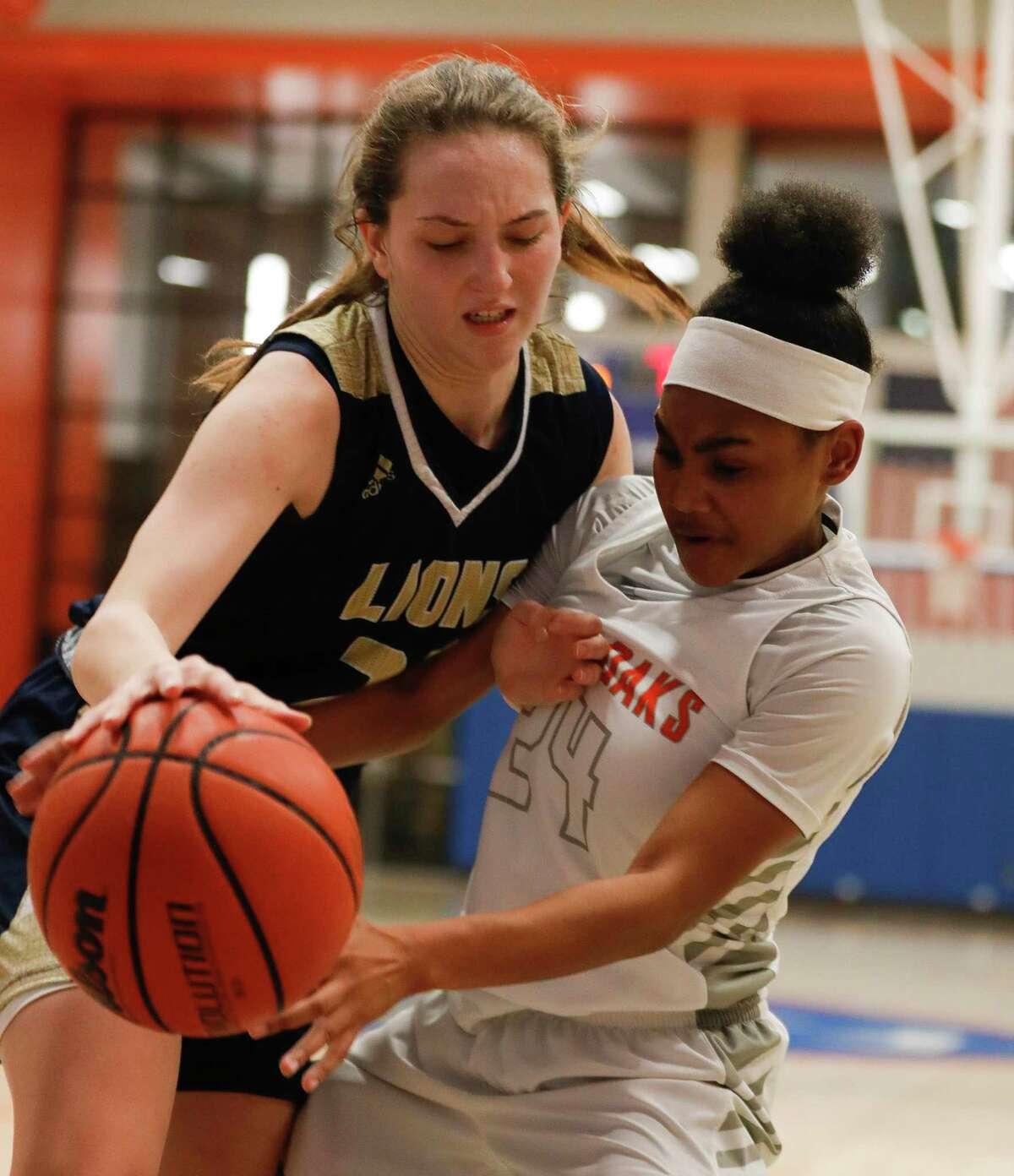Grand Oaks guard Kaitlyn Stewart (24) fouls Lake Creek forward Natalie Murdock (25) during the second quarter of a District 20-5A high school basketball game at Grand Oaks High School, Friday, Jan. 17, 2020, in Spring.