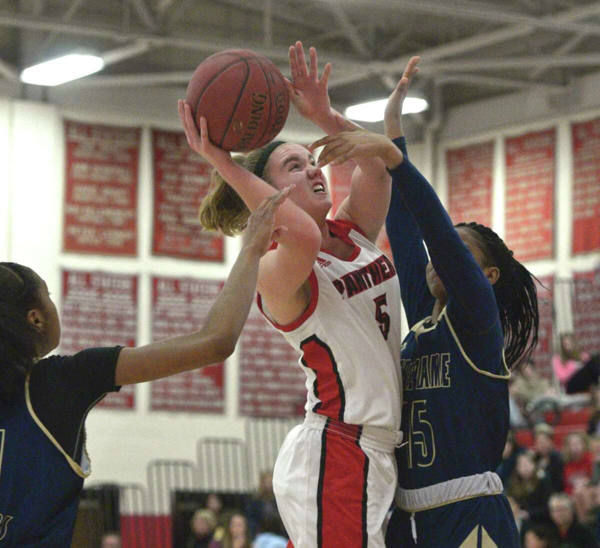Pomperaug's Molly Flanagan (5) drives to the basket between Notre Dame-Fairfield teammates Kayla Tilus (11) and Ciara Brown (15) in the girls basketball game on Friday night at Pomberaug High School in Southbury.
