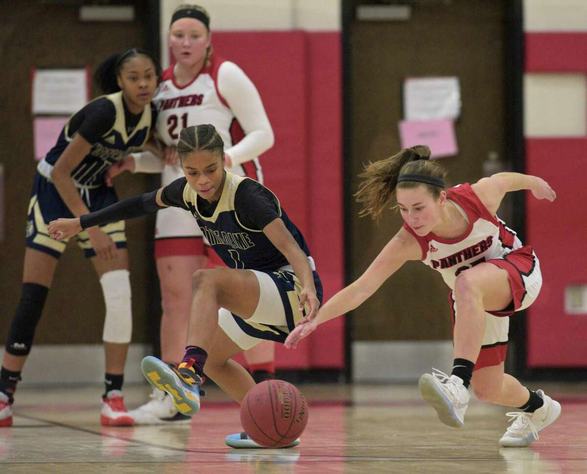 Notre Dame-Fairfield's Yamani McCollough (1) and Pomperaug's Madison Villa (35) dive for a loose ball in the girls basketball game on Friday night at Pomperaug High School in Southbury.