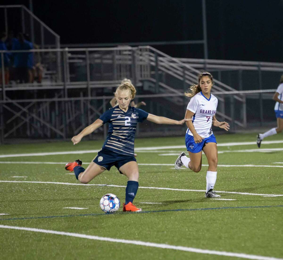 Lake Creek forward Katelyn Denley (2) passes the ball with Grand Oaks midfielder Analise Caudle (7) trailing behind in a District 20-5A girls soccer game in Montgomery on Friday, January 17, 2020.