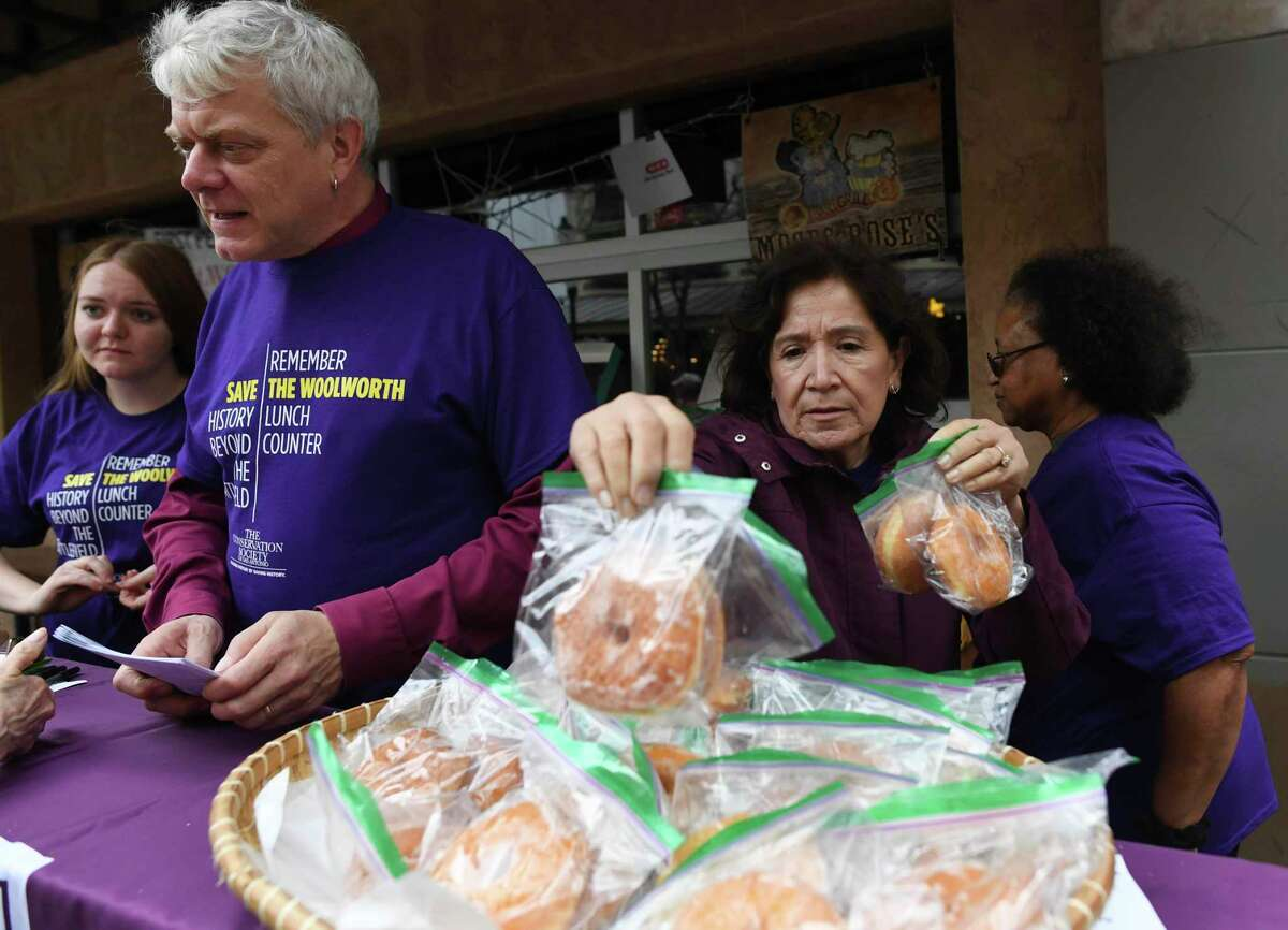 Leticia Diaz stacks donuts during a donut giveaway and educational event put on by The San Antonio Conservation Society and the Coalition for the Woolworth Building in downtown San Antonio on Friday, Jan. 17, 2020. The San Antonio Woolworth store's lunch counter was peacefully desegregated in 1960, a step leading to the passage of the Civil Rights Act of 1964. The building, which some call historic because of its importance in the fight for civil rights, is in danger of demolition because it is not included in any of the conceptual drawings of the Alamo Plan passed in 2018.