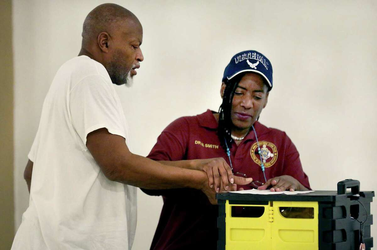 Norman Johns, 60, left, has his finger prints made by Nicole Smith a volunteer with the SAPD Family Assistance Crisis Team, to check his identity with prison records. Johns had all his personal information stolen from his house while he was in prison.