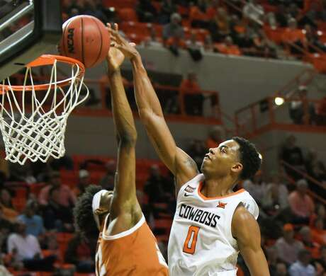 Oklahoma State guard Avery Anderson III (0) dunks over Texas forward Kai Jones (22) during the first half of an NCAA college basketball game in Stillwater, Okla., Wednesday, Jan. 15, 2020. (AP Photo/Brody Schmidt)