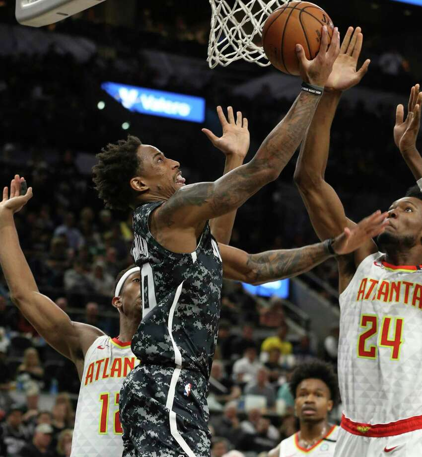 Spurs' DeMar DeRozan (10) goes to the basket against Atlanta Hawks' De'Andre Hunter (12) and Bruno Fernando (24) during their game at the AT&T Center on Friday, Jan. 17, 2020. Photo: Kin Man Hui, San Antonio Express-News / Staff Photographer / **MANDATORY CREDIT FOR PHOTOGRAPHER AND SAN ANTONIO EXPRESS-NEWS/NO SALES/MAGS OUT/ TV OUT