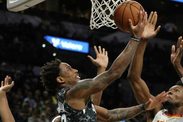 Spurs' DeMar DeRozan (10) goes to the basket against Atlanta Hawks' De'Andre Hunter (12) and Bruno Fernando (24) during their game at the AT&T Center on Friday, Jan. 17, 2020.