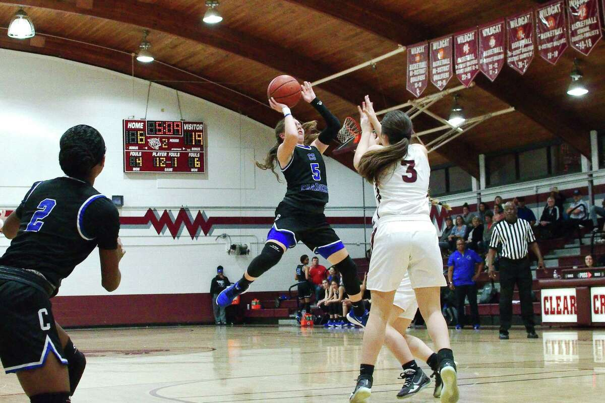 Clear Springs' Kylie Minter (5) puts up an off-balance shot over Clear Creek's Helene Carney (2) and Lili Pena (3) Friday at Clear Creek High School.
