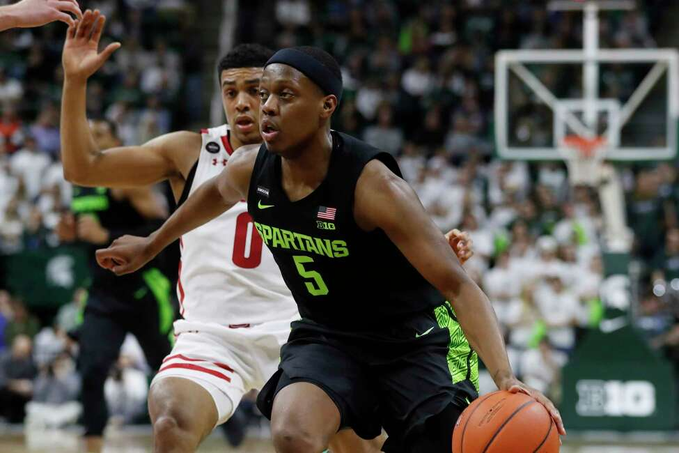 Michigan State guard Cassius Winston (5) drives on Wisconsin guard D'Mitrik Trice (0) during the second half of an NCAA college basketball game, Friday, Jan. 17, 2020, in East Lansing, Mich. (AP Photo/Carlos Osorio)