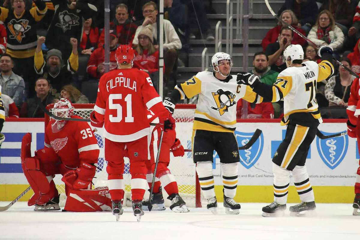 DETROIT, MICHIGAN - JANUARY 17: Sidney Crosby #87 of the Pittsburgh Penguins celebrates his game winning overtime goal with Evgeni Malkin #71 next to Jimmy Howard #35 of the Detroit Red Wings at Little Caesars Arena on January 17, 2020 in Detroit, Michigan. Pittsburgh won the game 2-1 in overtime. (Photo by Gregory Shamus/Getty Images)