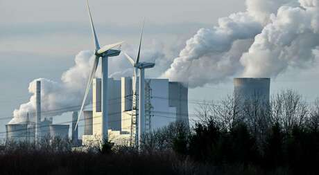 The RWE Niederaussem lignite-fired power station releases steam, behind two renewable energy producing wind turbines in Bergheim, Germany, Monday, Jan. 13, 2020. Germany plans an entirely coal phase out and to shut down all remaining coal-fired plants by 2038. (AP Photo/Martin Meissner)