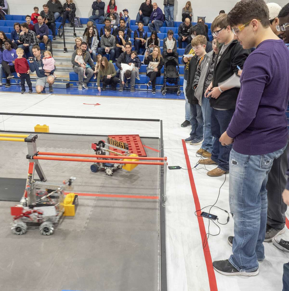 Members of Midland High's Insane Boltz and UTPB Stem Academy's Robo Rampage work together in one of the competitions 01/18/2020 during the First Tech Challenge, SkyStone, building a structure on a platform in Beal Gym at Trinity School. Tim Fischer/Reporter-Telegram