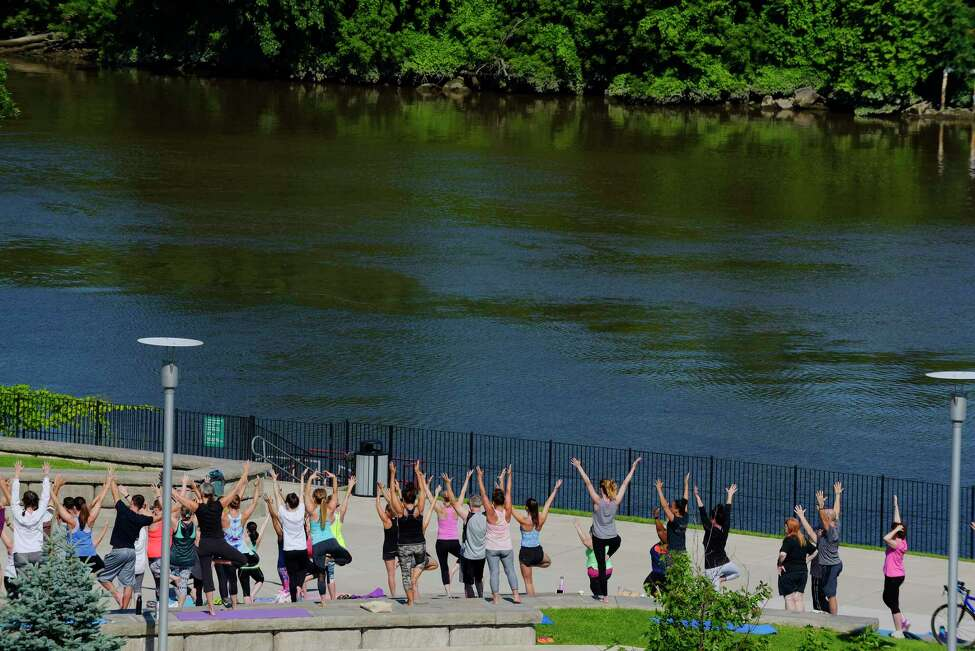 People take part in yoga near the Hudson River during the Fitness in the Park event at Riverfront Park on Sunday, July 9, 2017, in Troy, N.Y. The free yoga events are held at 9:00 am every Sunday through August 27th. (Paul Buckowski / Times Union)