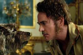 """This image released by Universal Pictures shows Dr. John Dolittle, portrayed by Robert Downey Jr., right, with Jip, voiced by Tom Holland, in a scene from """"Dolittle."""" (Universal Pictures via AP)"""