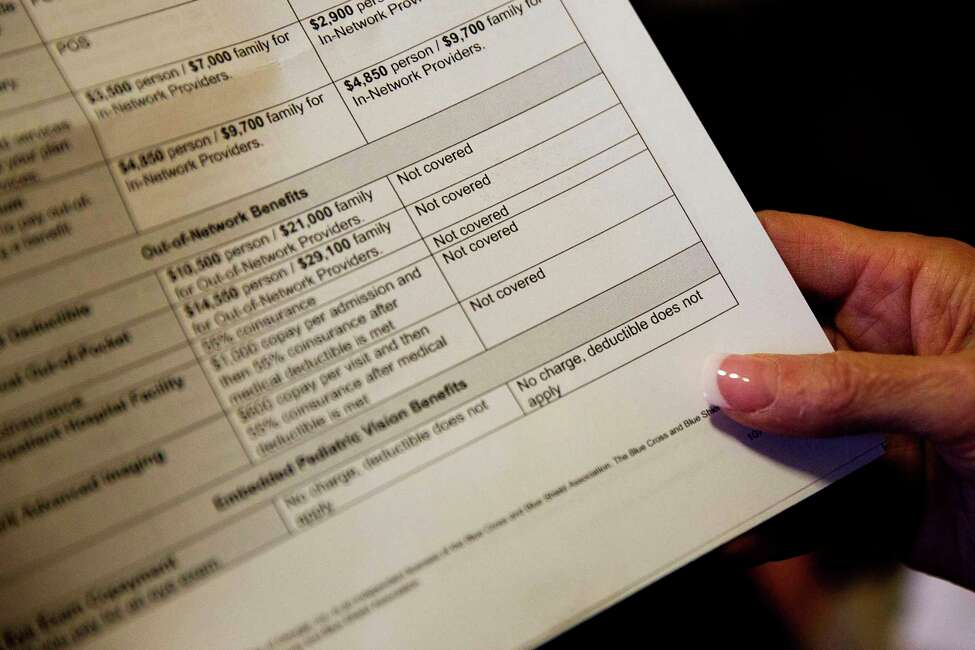 FILE - In this Dec. 4, 2017 file photo, a person looks over a health insurance benefit comparison chart in Georgia. The new year often starts harshly for people with high-deductible health insurance. Many of those deductibles reset Jan. 1, forcing patients to pay thousands of dollars for care before most coverage starts. (AP Photo/David Goldman, File)