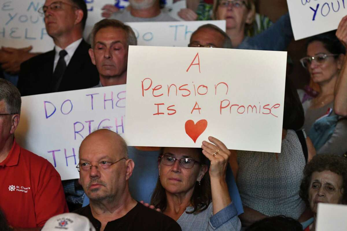 St. Clare'sHospital retirees and workers display signs during a press conference where lawmakers urged the state to launch an investigation of the hospital's pension fund collapse on Monday, June 17, 2019, at the Capitol in Albany, N.Y. Last year, over 1,000 former employees and retirees were notified their pensions would be eliminated or significantly decrease. (Will Waldron/Times Union)