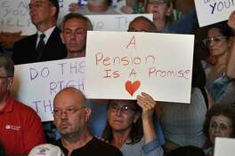 St. ClareA?•s Hospital retirees and workers display signs during a press conference where lawmakers urged the state to launch an investigation of the hospital's pension fund collapse on Monday, June 17, 2019, at the Capitol in Albany, N.Y. Last year, over 1,000 former employees and retirees were notified their pensions would be eliminated or significantly decrease. (Will Waldron/Times Union)