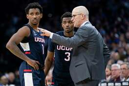 UConn coach Dan Hurley, right, talks things over with Christian Vital, left, and Alterique Gilbert, center, during the second half of a game against Villanova on Jan. 18 in Philadelphia.