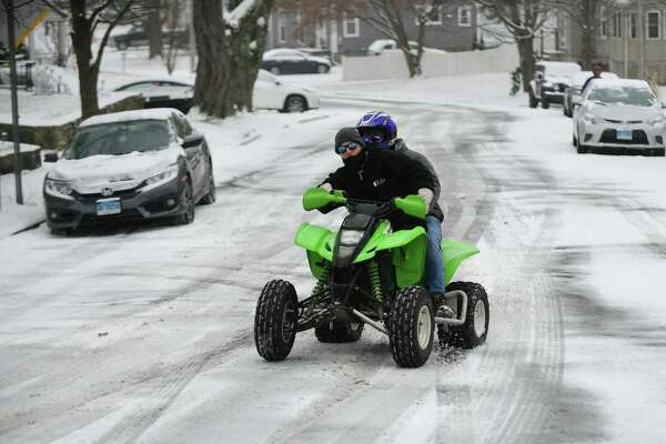 Quad riders make their way up Raymond Terrace in the snow Saturday, Januray 18, 2020, in Norwalk, Conn. The eealier than forecast snowfall caught residents off guard.