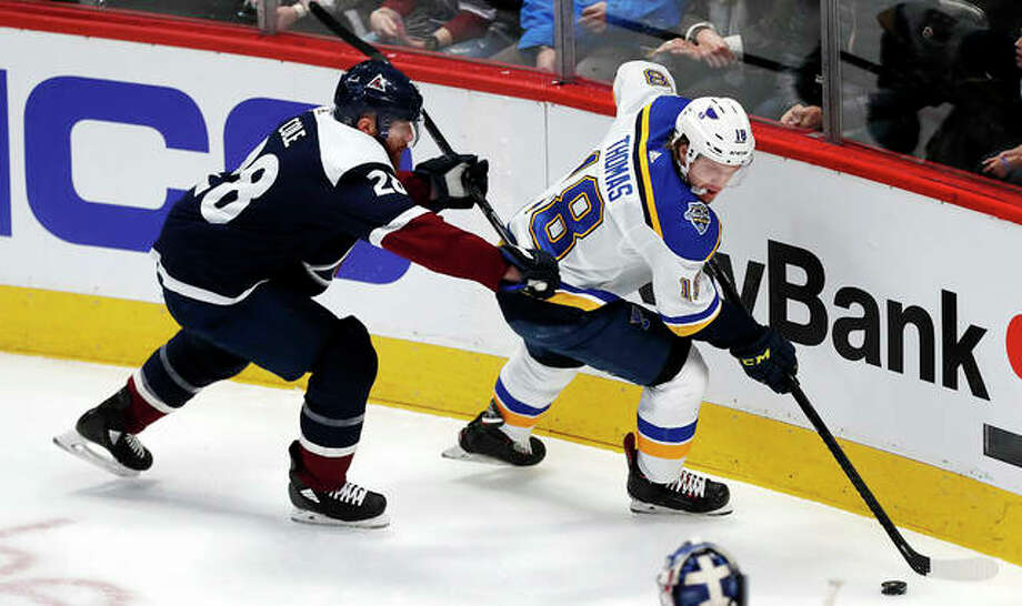 Blues center Robert Thomas, right, collects the puck as Colorado Avalanche defenseman Ian Cole covers in the first period of Saturday's game in Denver. Photo: AP Photo