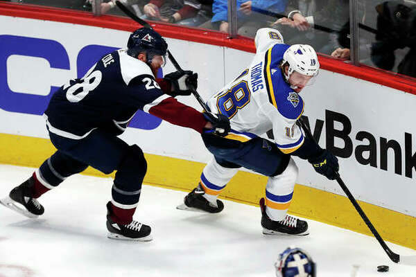 Blues center Robert Thomas, right, collects the puck as Colorado Avalanche defenseman Ian Cole covers in the first period of Saturday's game in Denver.