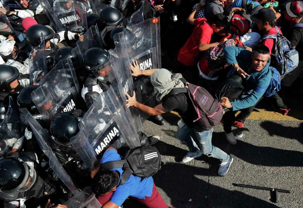 Migrants charge on Mexican National Guardsmen at the border crossing between Guatemala and Mexico in Tecun Uman, Guatemala, Saturday, Jan. 18, 2020. More than a thousand Central American migrants surged onto a bridge spanning the Suchiate River that marks the border between both countries as Mexican security forces attempted to impede their journey north. (AP Photo/Marco Ugarte)