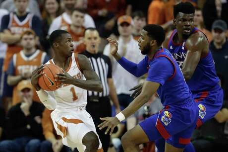Texas guard Andrew Jones tries to deal with pressure from Kansas' Isaiah Moss, center, and Udoka Azubuike in the first half.