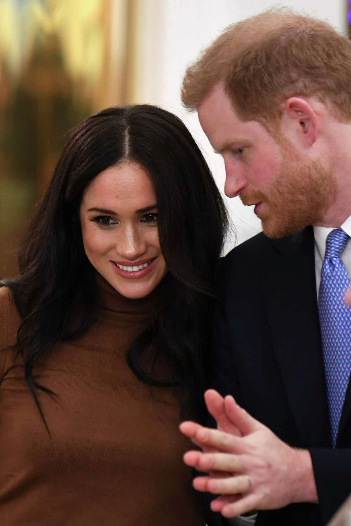 (FILES) In this file photo taken on January 07, 2020 Britain's Prince Harry, Duke of Sussex and Meghan, Duchess of Sussex react during their visit to Canada House in thanks for the warm Canadian hospitality and support they received during their recent stay in Canada, in London. - Britain's Prince Harry and his wife Meghan will give up their titles and stop receiving public funds following their decision to give up front-line royal duties, Buckingham Palace said on January 18, 2020.