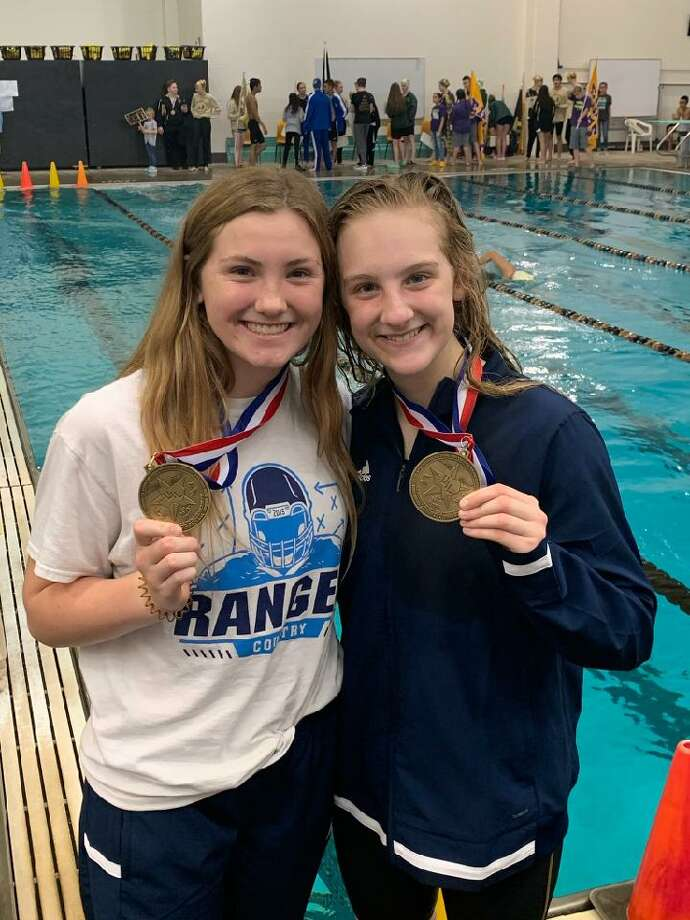Greenwood diver Grace Austin, left, and Greenwood swimmer Kaitlin Geric pose with their gold medals after qualifying for regionals at the District 4-5A Swimming & Diving Championships in Andrews. Photo: Courtesy Photo