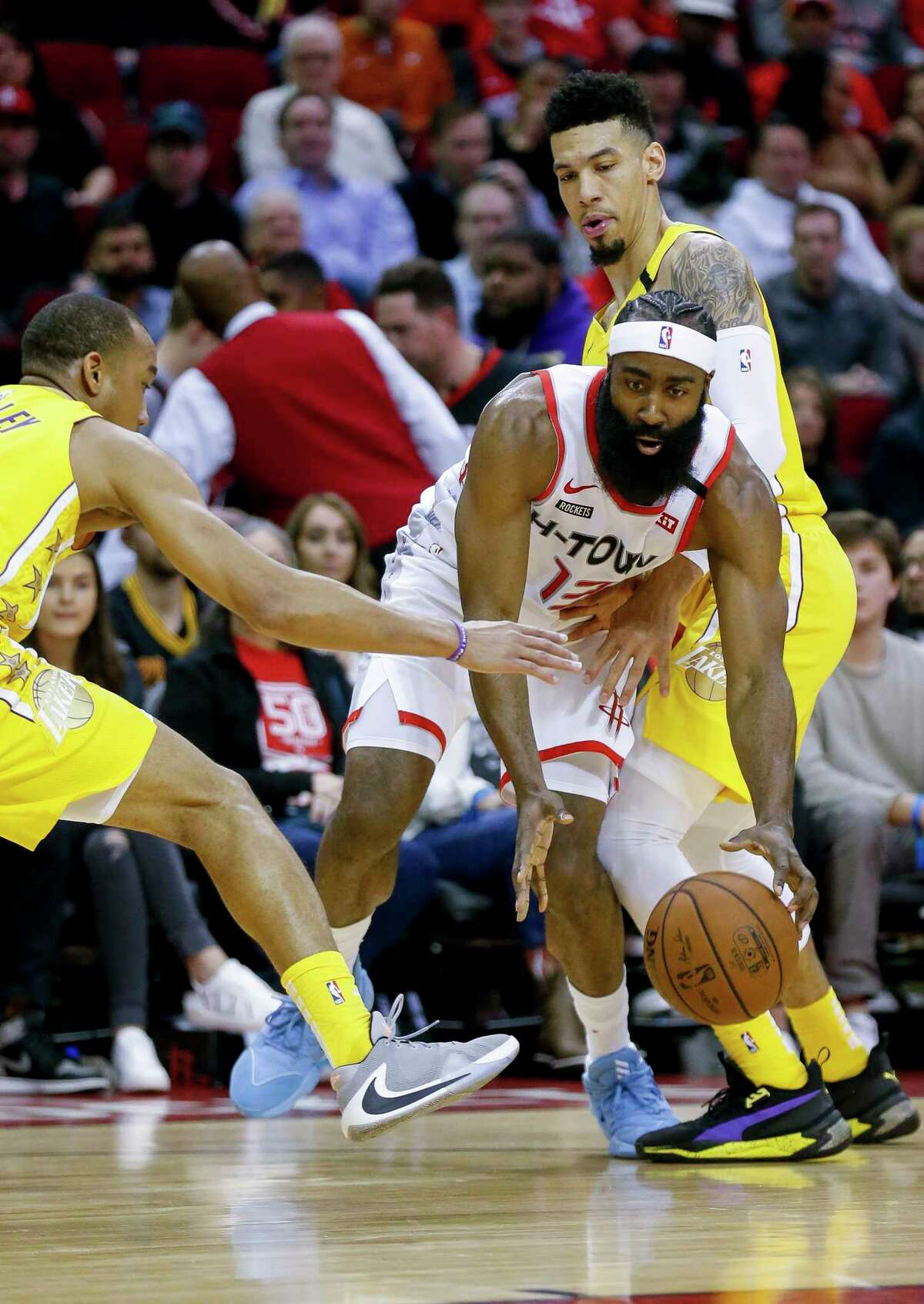 Houston Rockets guard James Harden (13) makes his way through two Los Angeles Lakers players during the first half of an NBA game at the Toyota Center on Saturday, Jan. 18, 2020.