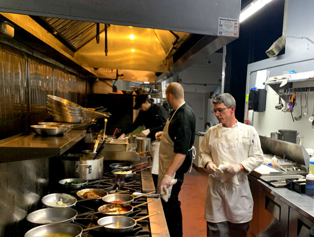 Brian Bowden, right, in his new kitchen at at Radici Kitchen & Bar in January 2020. All staff members now wear masks. (Steve Barnes/Times Union.)