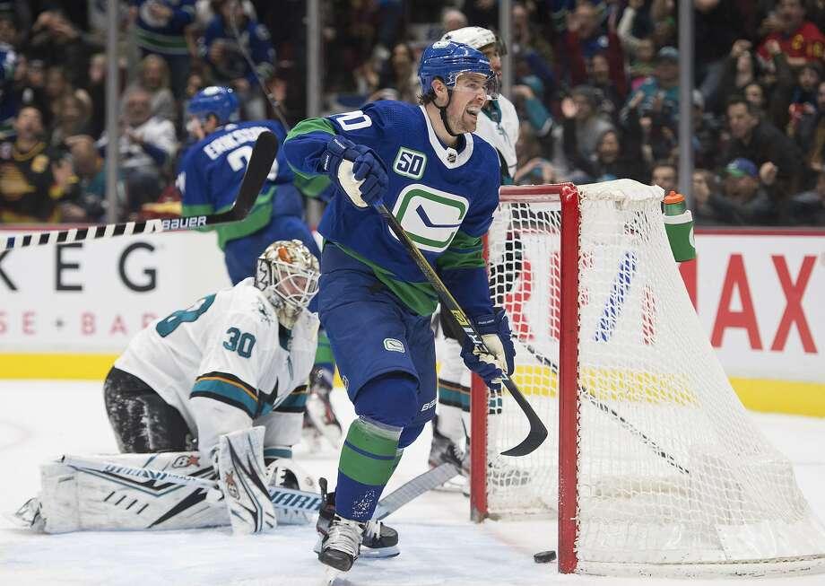 Sharks goaltender Aaron Dell gets up as Vancouver Canucks center Brandon Sutter celebrates a goal. Photo: Jonathan Hayward / Associated Press