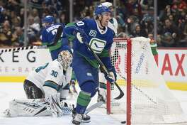 San Jose Sharks goaltender Aaron Dell (30) gets up as Vancouver Canucks centre Brandon Sutter (20) celebrates a goal by Loui Eriksson during the second period of an NHL hockey game Saturday, Jan. 18, 2020, in Vancouver, British Columbia. (Jonathan Hayward/The Canadian Press via AP)
