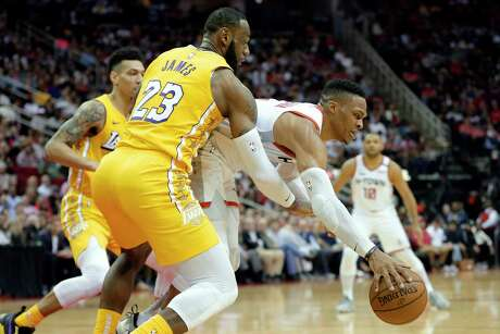 Los Angeles Lakers forward LeBron James (23) reaches in as Houston Rockets guard Russell Westbrook tries to keep control of the ball during the second half of an NBA basketball game Saturday, Jan. 18, 2020, in Houston. (AP Photo/Michael Wyke)