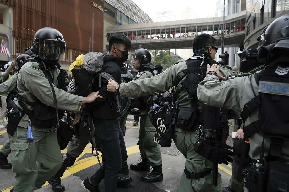 Riot police detain a protester in Hong Kong. Officers also arrested the organizer of the demonstration. Photo: Kin Cheung / Associated Press