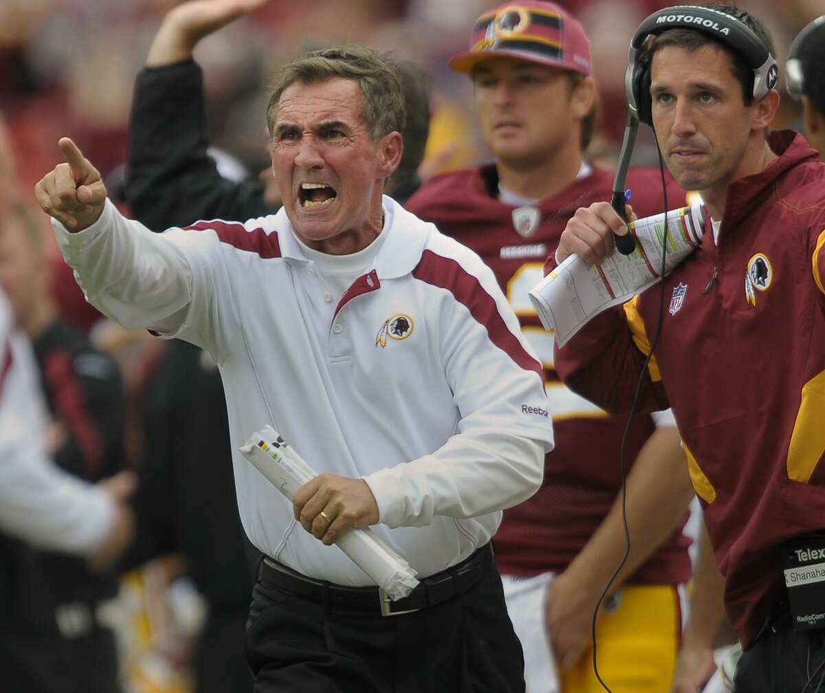 Washington head coach Mike Shanahan , left, gets the ref's attention to call a time out in the final minute of the game in 2011. His son, offensive coordinator Kyle Shanahan, is seen at right.