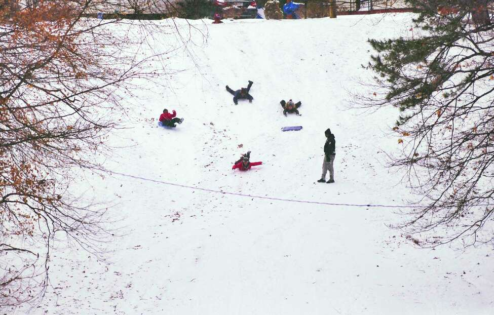 With fresh snow on the ground, children slide down a hill in Central Park on Sunday, Jan. 19, 2020, in Schenectady, N.Y. (Paul Buckowski/Times Union)