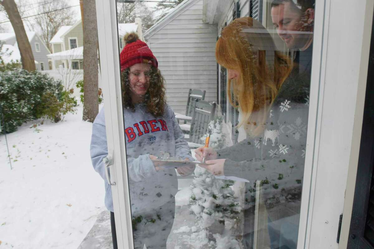 Caroline McGraw, left, gets signatures from Ginger LaChapelle, center, and her husband, Bill Duffy, at their home on Sunday, Jan. 19, 2020, in Niskayuna, N.Y. McGraw was out getting signatures because she is running to be a DNC delegate for Joe Biden. (Paul Buckowski/Times Union)