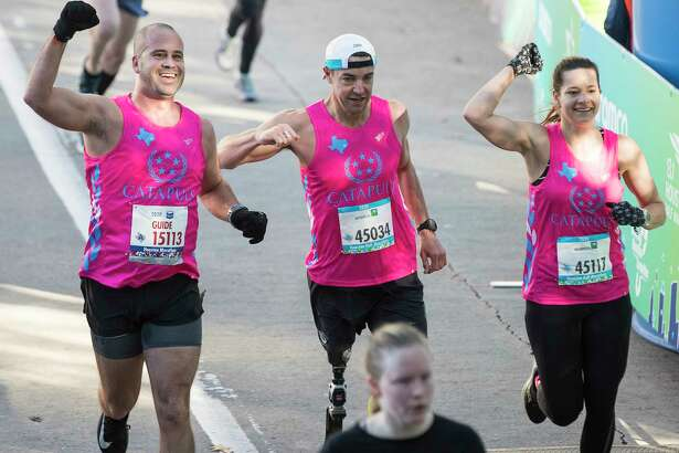 Greg Orphanides, left, Mark Barr and Morgan Dean celebrate as they cross the finish line of the Aramco Half Marathon Sunday, Jan. 19, 2020 in Houston.