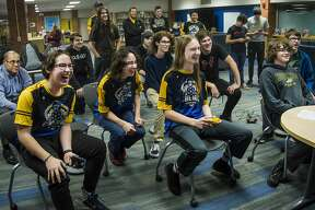 Midland High's Ryan Rinearson, third from left, plays a game of Super Smash Bros. against Dow High's Nathan Seidel, right, as other players, parents and coaches watch during the two schools' esports meet Friday, Jan. 17, 2020 at Midland High. (Katy Kildee/kkildee@mdn.net)