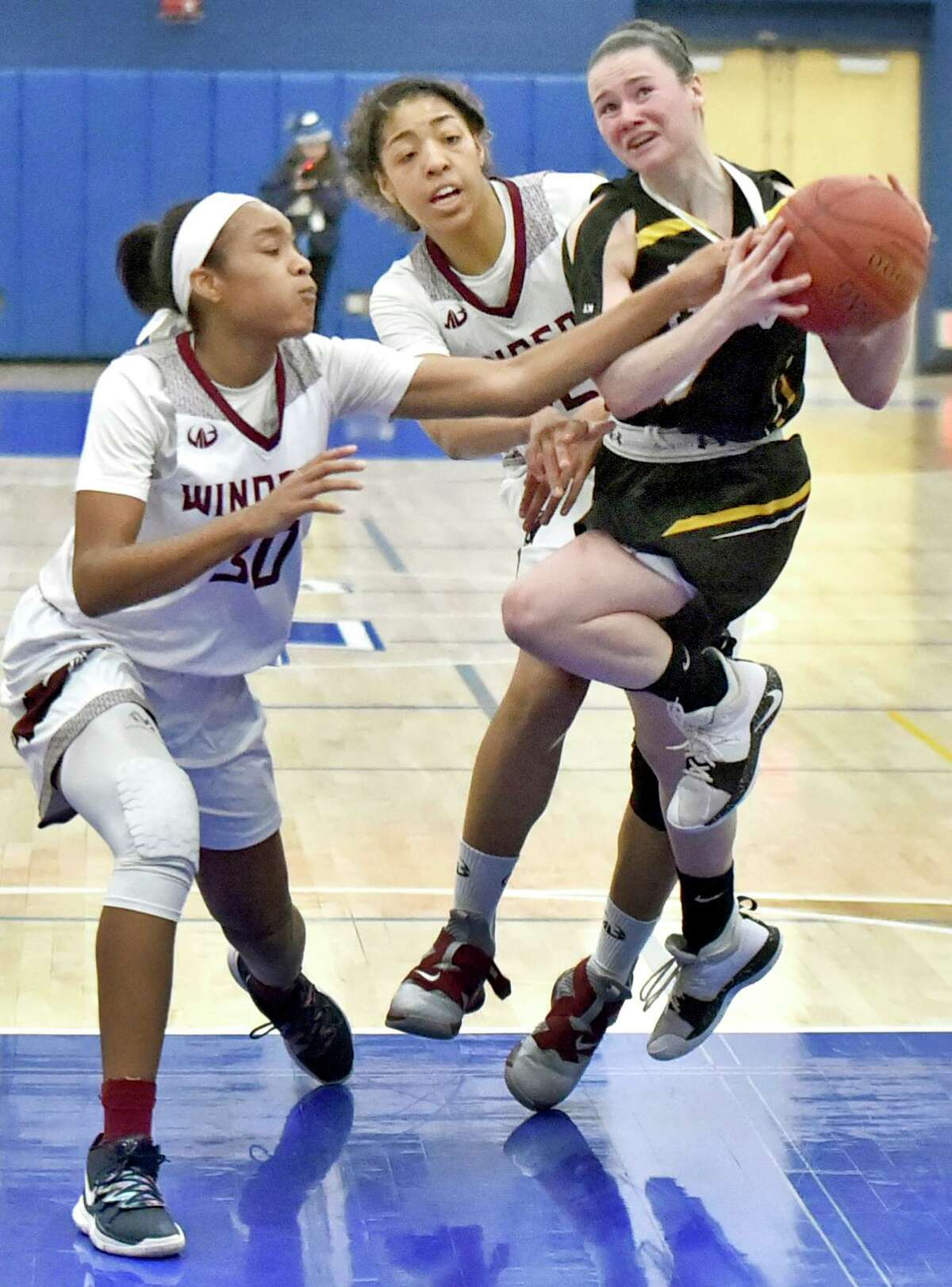 Azure Riley, left, and Denise Solis, center, of Windsor, play defense against a driving Sarah Wohlgemuth of Daniel Hand of Madison during the fourth quarter of the CIAC State girls basketball tournament semifinal game last season at Plainville High School. Hand defeated Windsor 33-27.