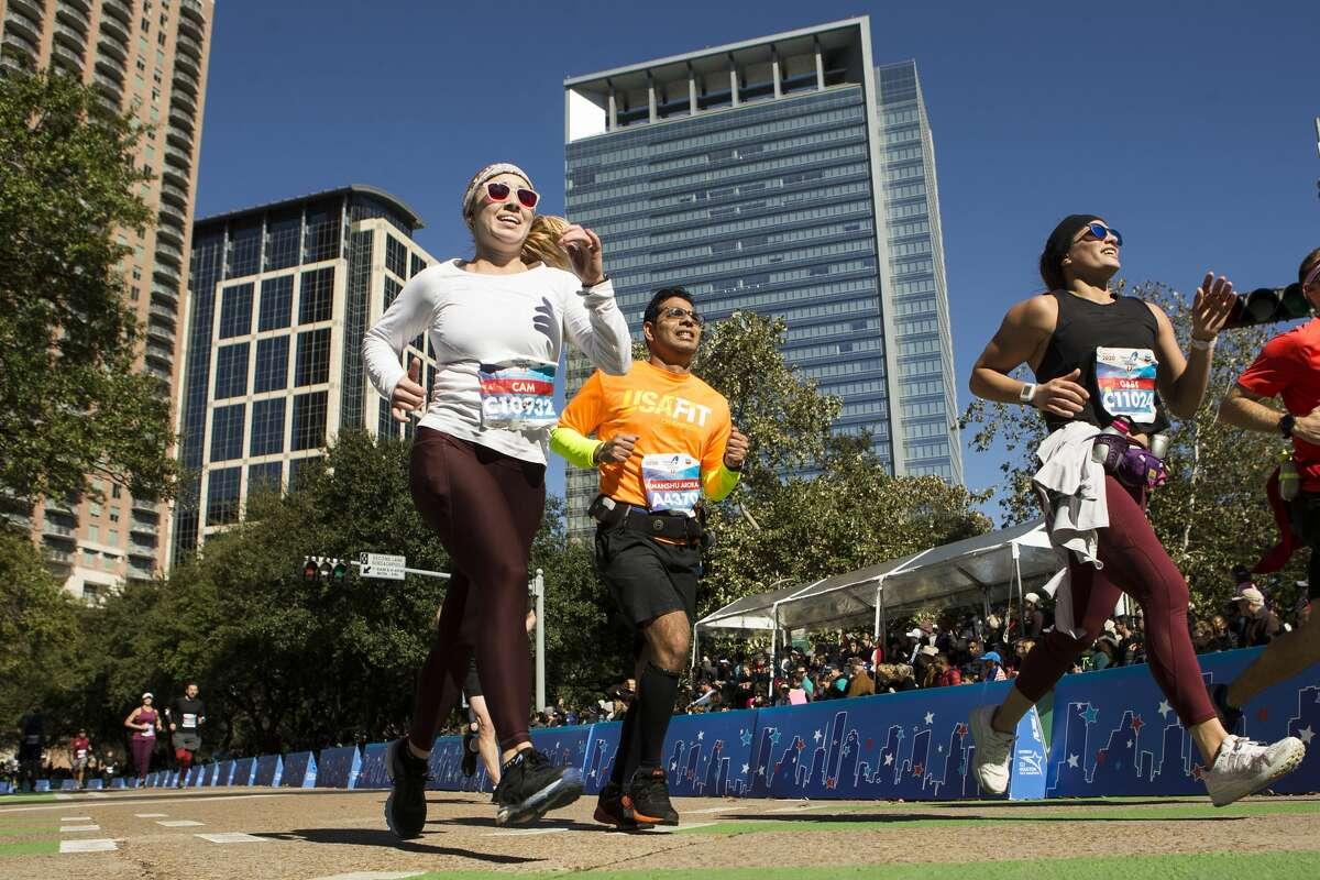 Cameron Koday, left, Himanshu Aroa, and Gabriella Serrati runs down the final stretch toward the finish line of the Chevron Houston Marathon Sunday, Jan. 19, 2020 in Houston.